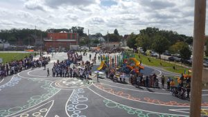 Children standing on asphalt playground decorated with colorful symbols