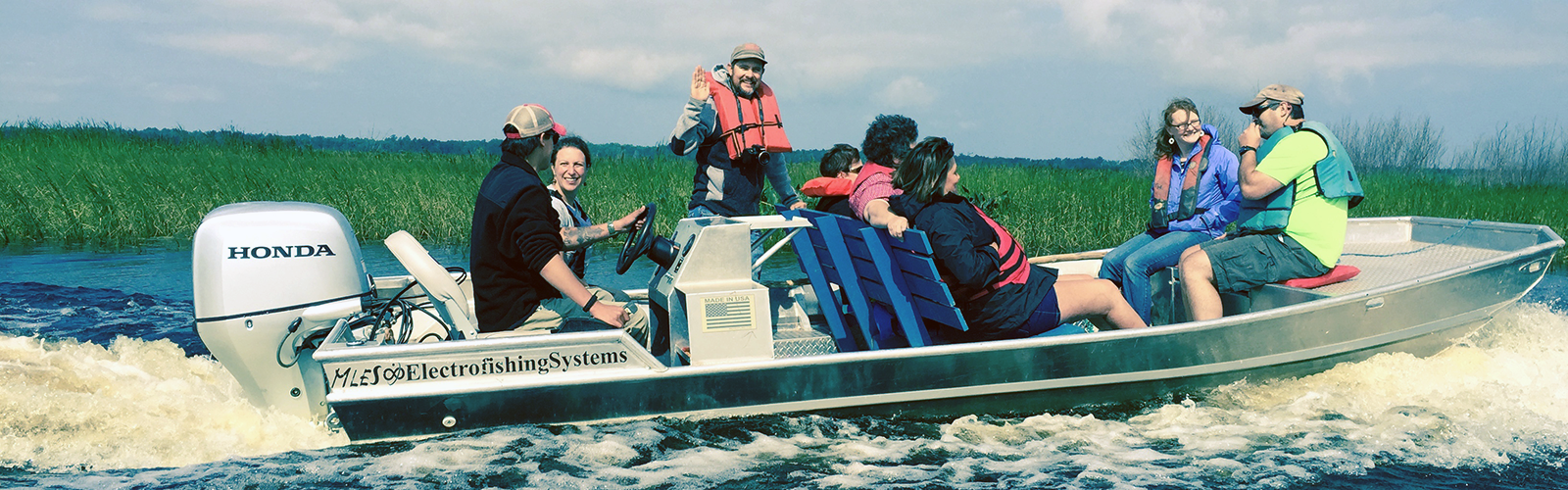 Motorboat cruises through Kakagon Sloughs with group of 8 participants, talking and smiling