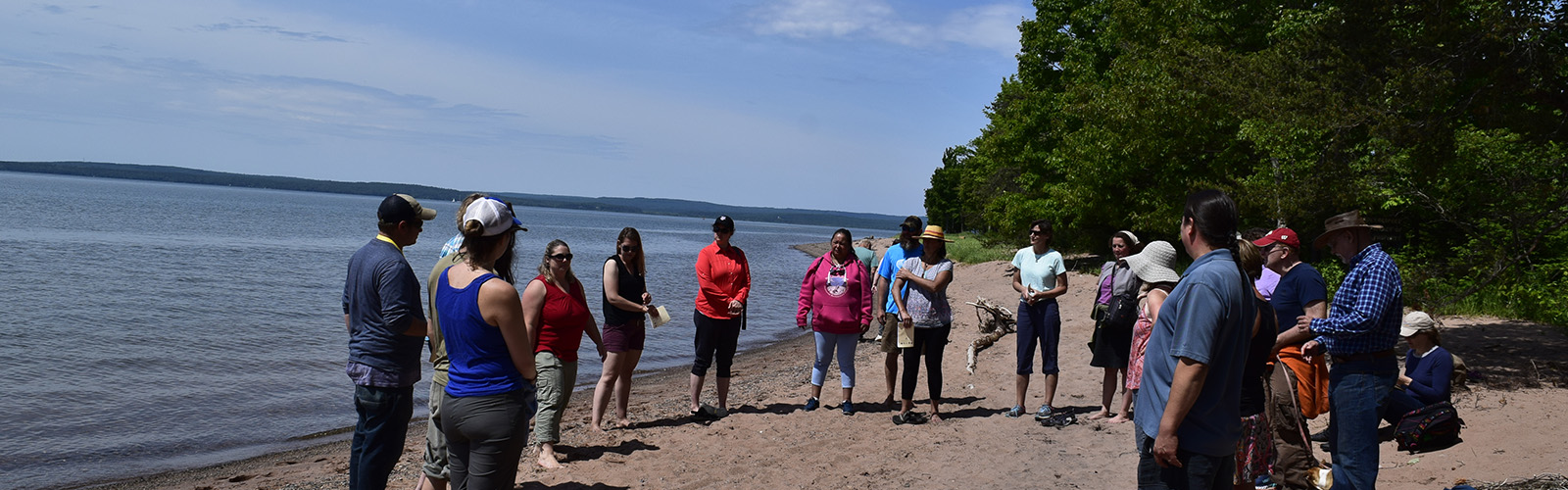 Participants stand in semi-circle on Madeline Island beach off of Lake Superior