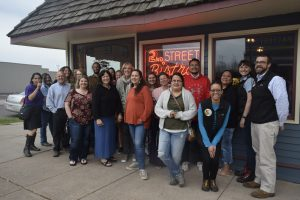 Advisory group stands in front of restaurant